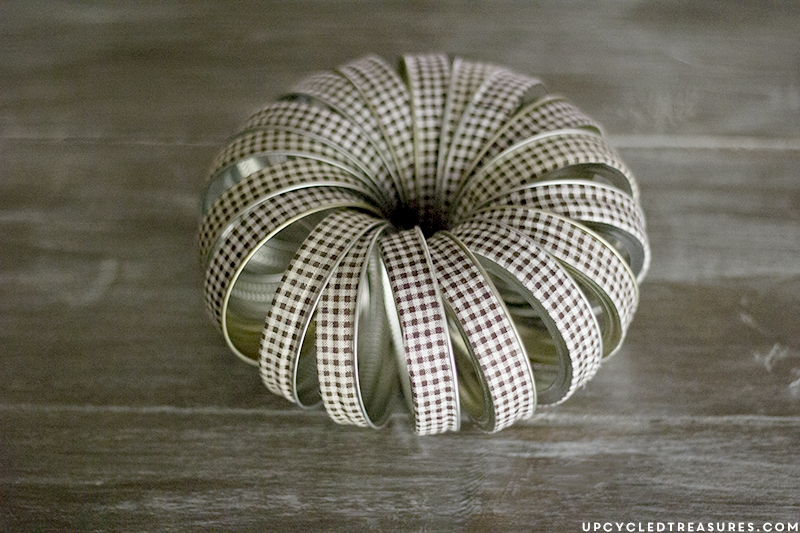 See how easy it is to create this rustic fall mason Jar lid pumpkin using canning lids, fabric tape, fishing line and a stick!