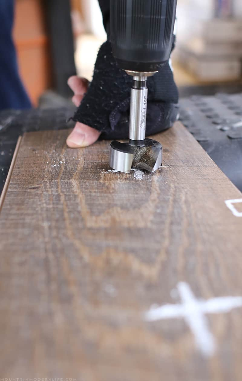 Creating hole in flooring with forstner bit to create space for bolts | MountainModernLife.com