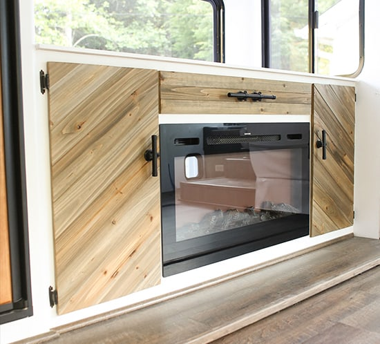 rustic-modern-cabinet-with-tv-lift-and-electric-fireplace-mountainmodernlife.com-550x498