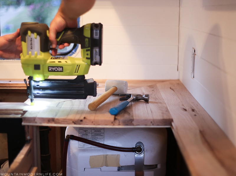 Looking for an affordable way to update your kitchen counters? Check out this post on how to Create Wood Counters from Flooring in a RV! MountainModernLife.com
