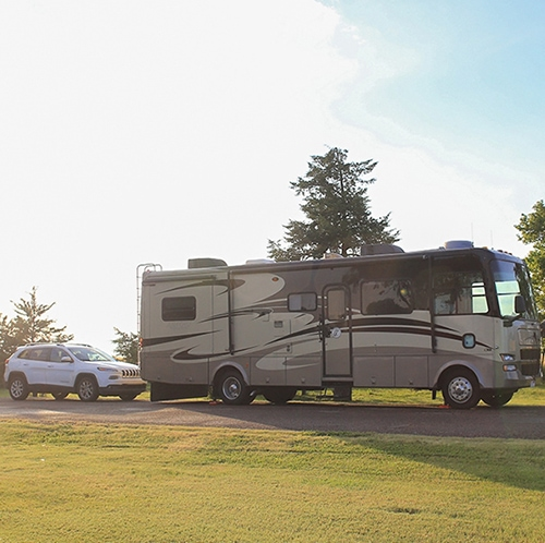 Our RV with the car behind it in the featured image for From Nowhere to Now here
