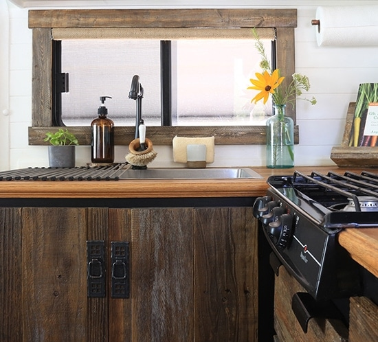 Thinking about renovating your camper? Come see how we used reclaimed wood to create a rustic modern RV kitchen! MountainModernLife.com