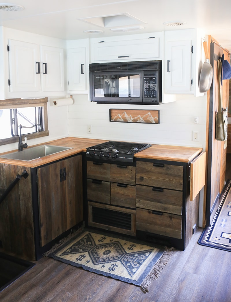 Thinking about renovating your camper? See how reclaimed wood was used to create a rustic modern RV kitchen! MountainModernLife.com