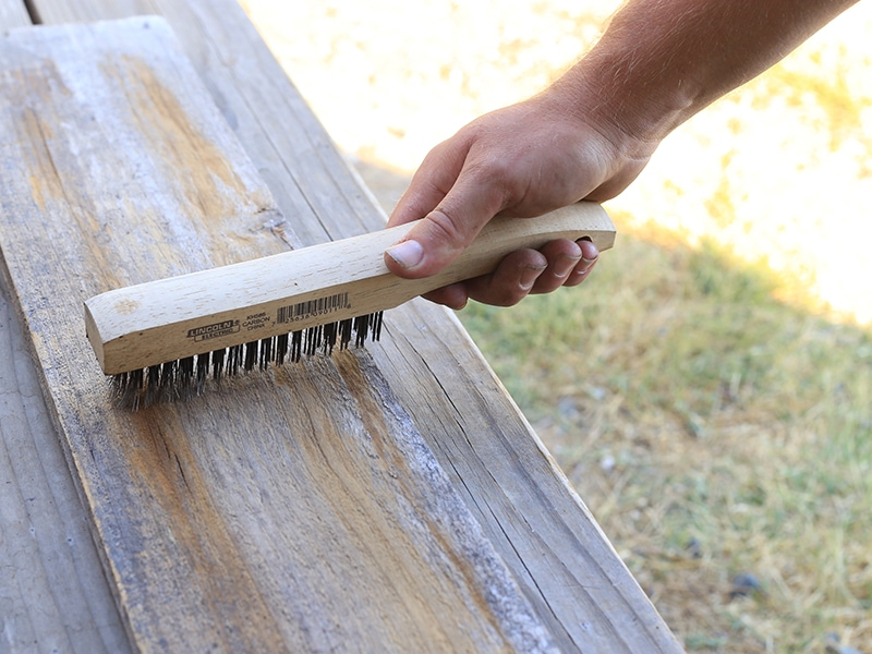 Cleaning reclaimed wood with a wire brush | MountainModernLife.com