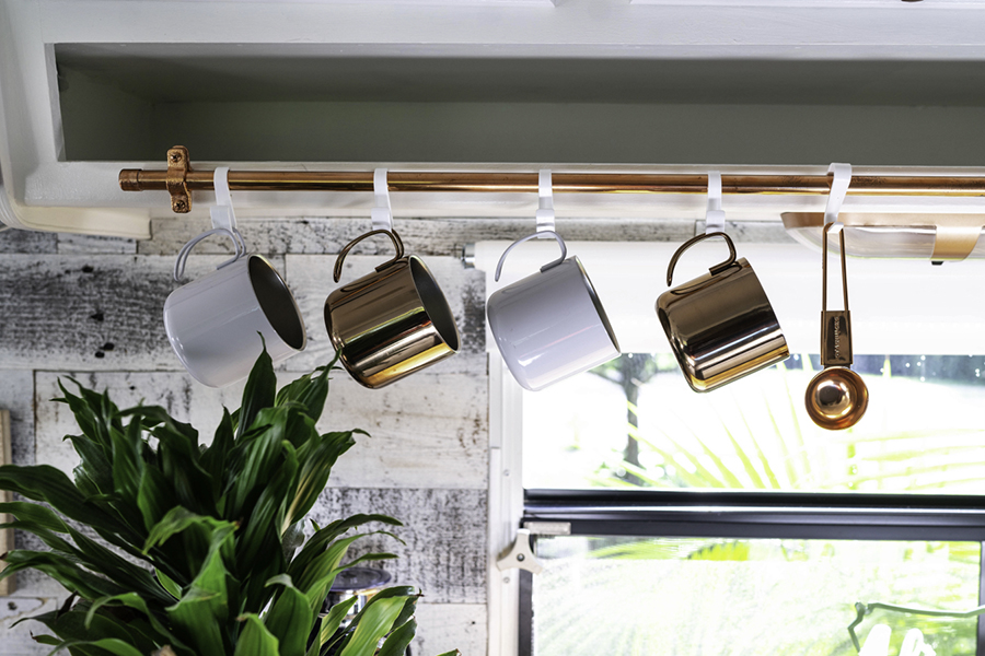 mugs hanging on copper pipe