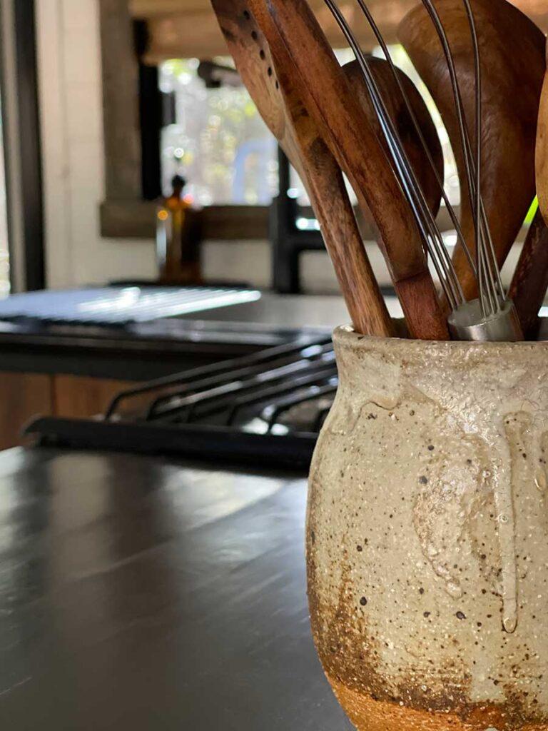 ceramic pot with wooden kitchen utensils